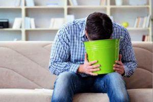 Hombre vomitando en un cubo